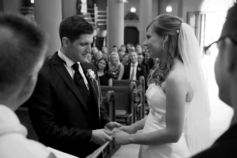 Das Brautpaar während der Trauung in der Kirche. Sie halten sich an den Händen. Schwarz-weiß-Foto.