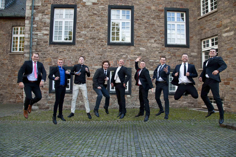 Der Bräutigam und seine Freunde springen in die Luft.