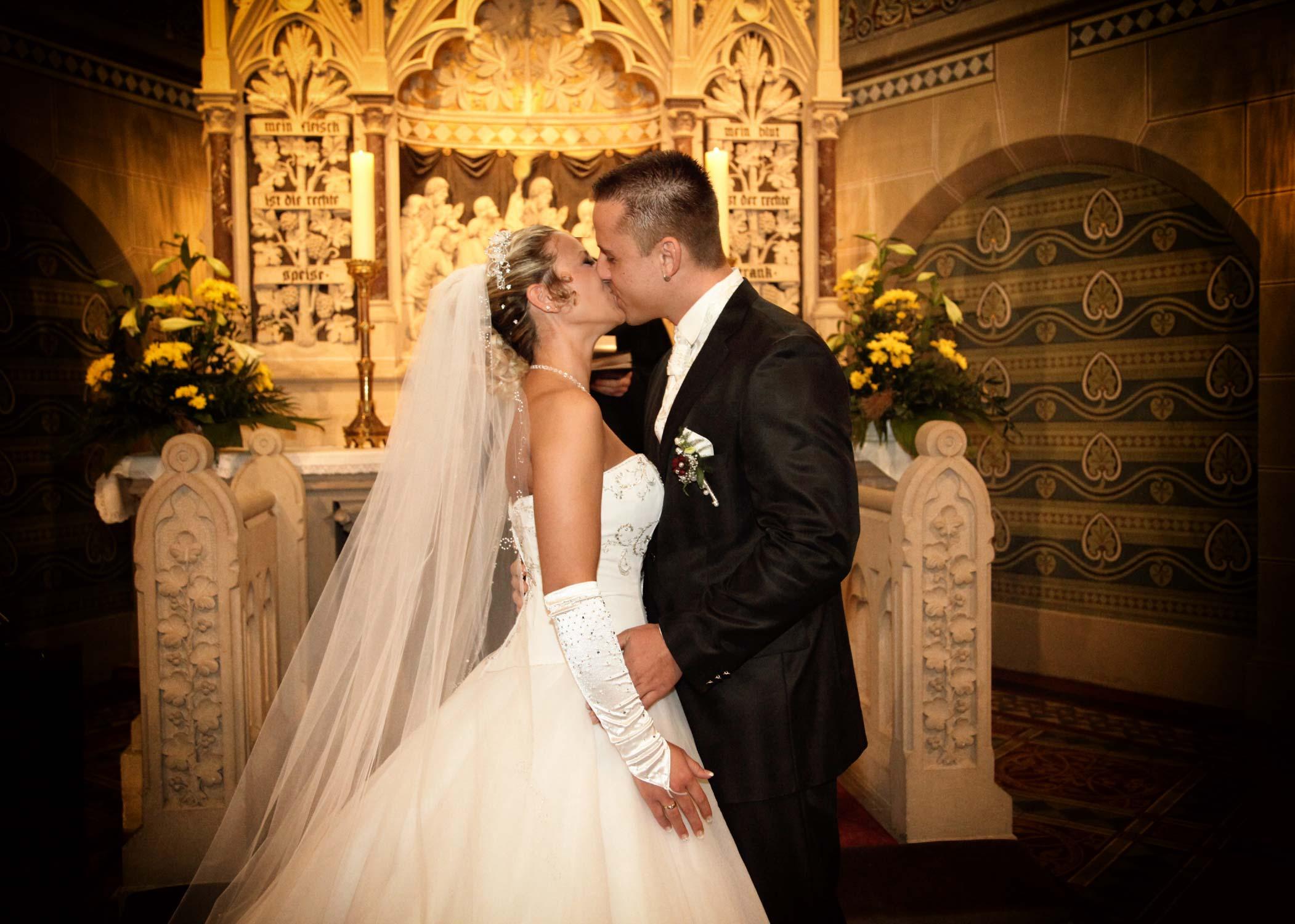 Der Hochzeitskuss. Das Brautpaar küsst sich vor dem goldenen Altar in der Kirche. Die Braut trägt einen langen weißen Schleier.