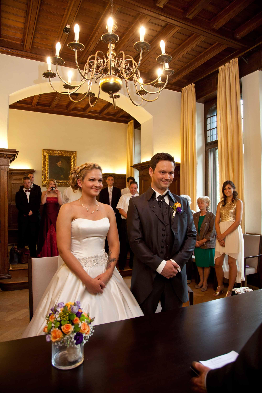 Das Brautpaar während der Trauung im Trausaal. Über den beiden ist ein großer Kronleuchter.
