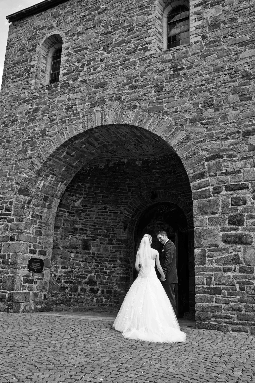 Das Brautpaar vor dem Eingang der Kirche. Schwarz-weiß-Foto.