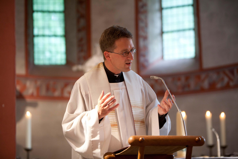 Der Pfarrer am Mikrofon in der Kirche. Er gestikuliert mit den Händen.