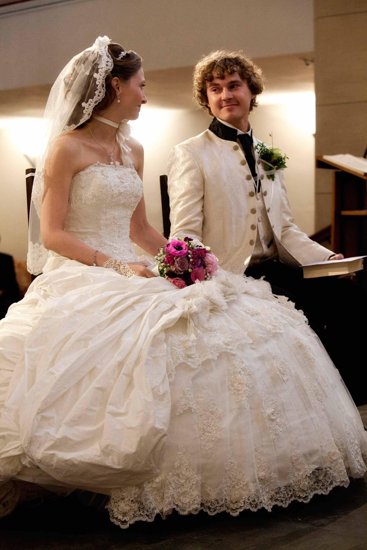 Das Brautpaar sitzt nebeneinander in der Kirche. Sie schauen sich an. Auf dem Schoß der Braut liegt der Brautstrauß. Der Bräutigam hält ein Gesangbuch in der Hand.