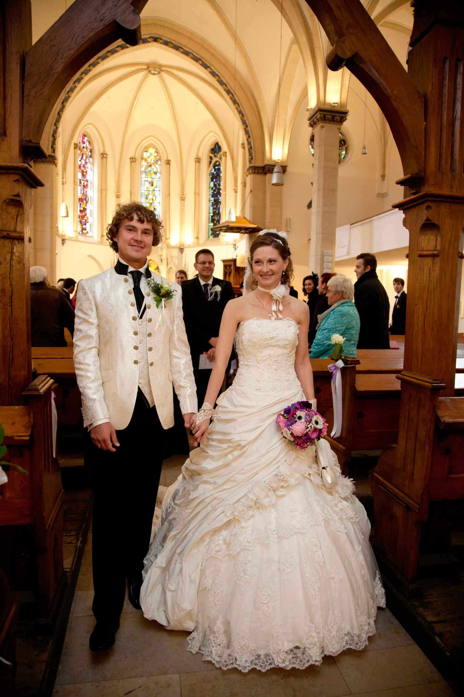 Auszug aus der Kirche. Das Brautpaar geht nebeneinander und Hand in Hand aus der Kirche.