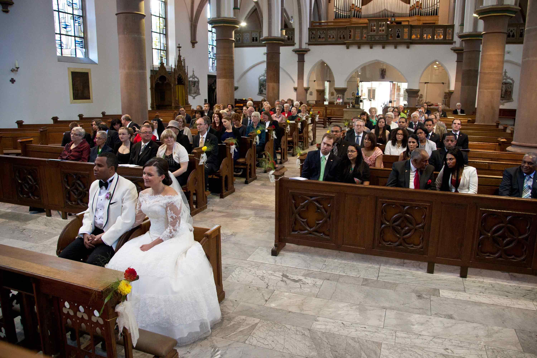 Das Brautpaar und die Hochzeitsgäste sitzen in der Kirche.