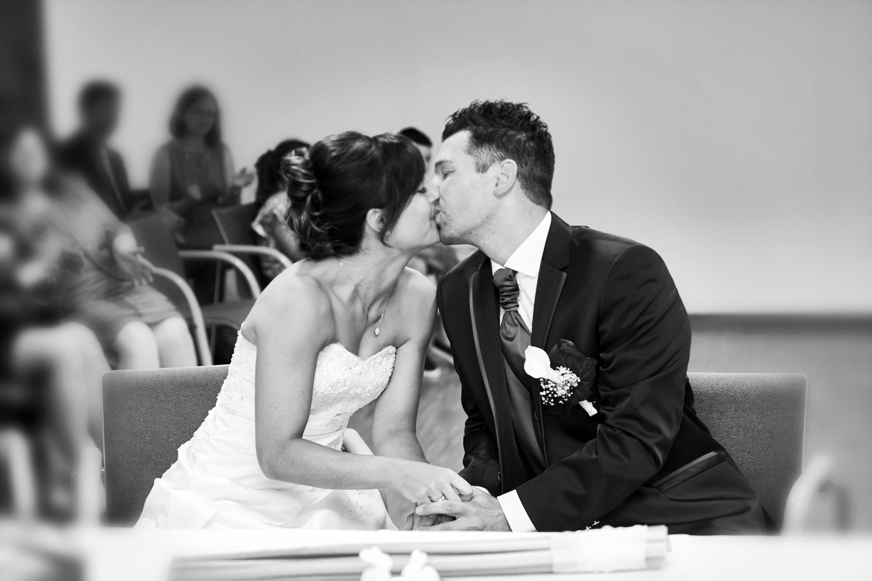 Der Hochzeitskuss des Brautpaares während der Trauung. Die beiden halten sich an den Händen. Im Hintergrund sieht man die Hochzeitsgäste. Schwarz-weiß-Foto.