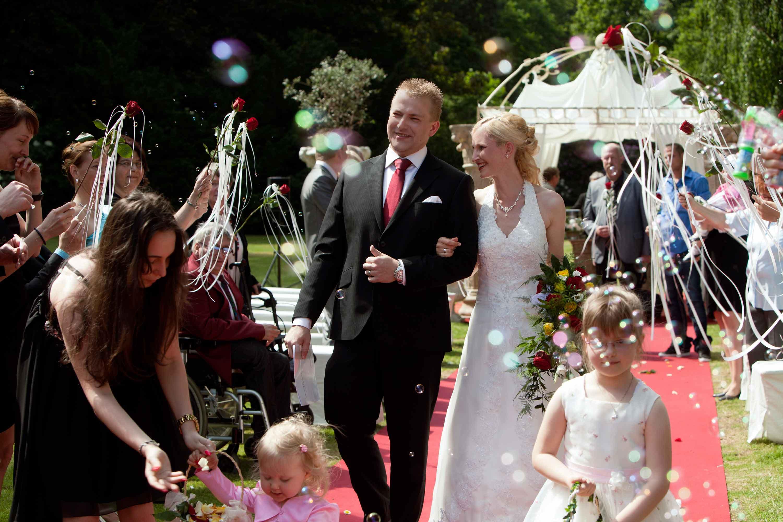 Das Brautpaar läuft nach der Trauung nebeneinander auf einem roten Teppich entlang. Die Braut hackt sich am Arm des Bräutigams ein. Sie sind umgeben von roten Rosen, ihren Hochzeitsgästen und Seifenblasen.