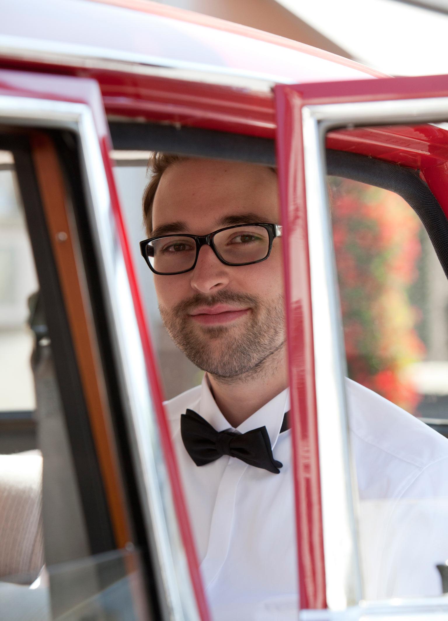 Der Bräutigam sitzt in einem roten Auto. Er trägt eine schwarze Brille und eine schwarze Fliege.