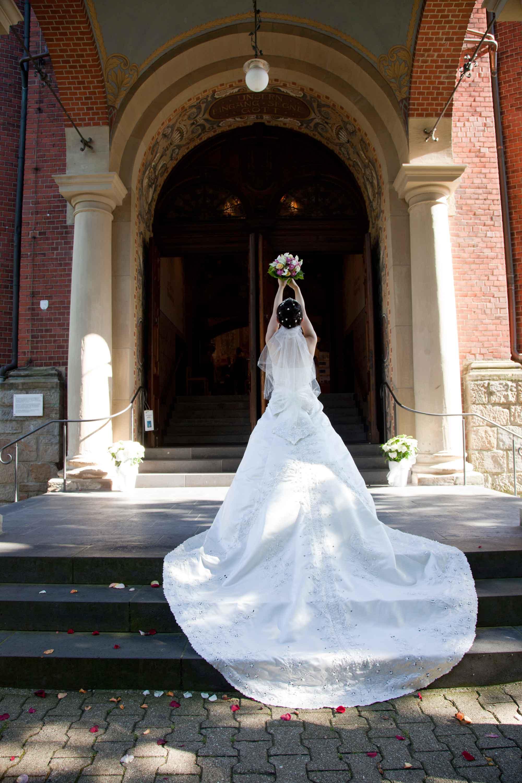 Die Braut streckt beide Arm mit dem Brautstrauß in die Höhe. Ihr langes, weißes Kleid liegt über der Treppe.