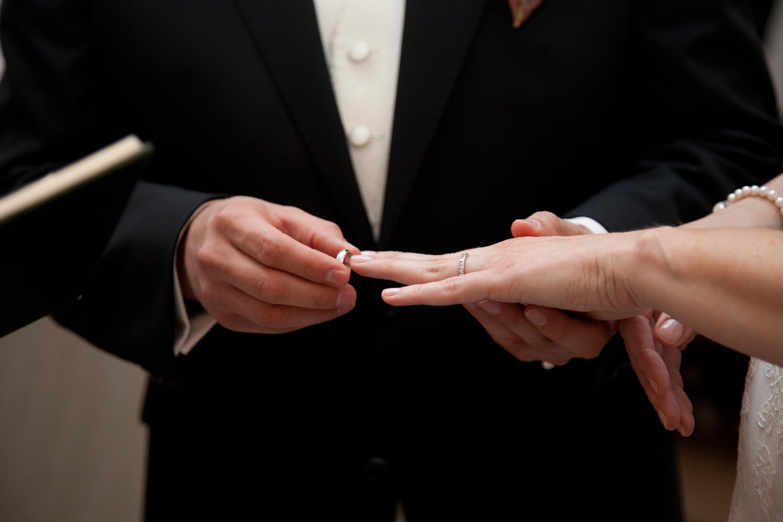 Anstecken des Eheringes an die Hand der Braut. Detailaufnahme.
