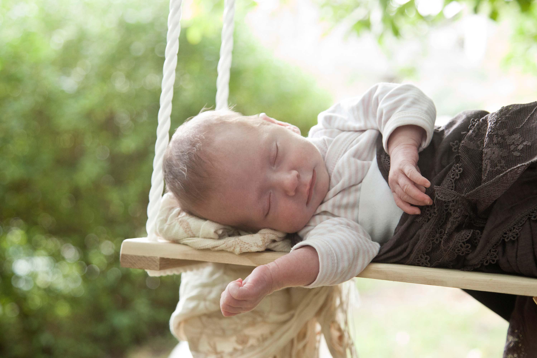 Das Baby schläft auf einer Schaukel. Es ist in Tücher eingewickelt.