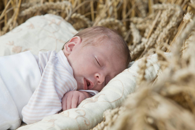 Baby im Kornfeld. Das Baby schläft friedlich auf einer hellen Decke mit geöffnetem Mund.