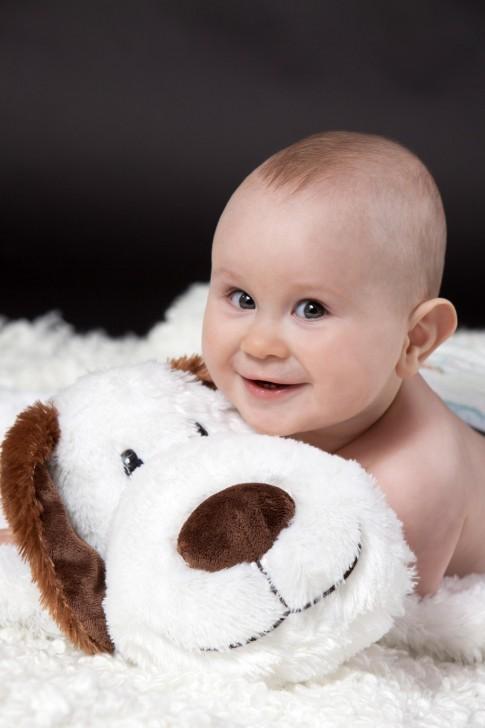 Das Baby schaut in die Kamera. Es lacht und kuschelt sich an sein Kuscheltier. Auch das Kuscheltier lächelt.