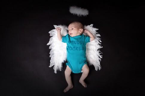 Baby mit weißen Engelflügeln. Im türkisfarbenem Strampler, auf dem steht Windelrocker. Über dem Kopf schwebt ein weißer, federner Heiligenschein.