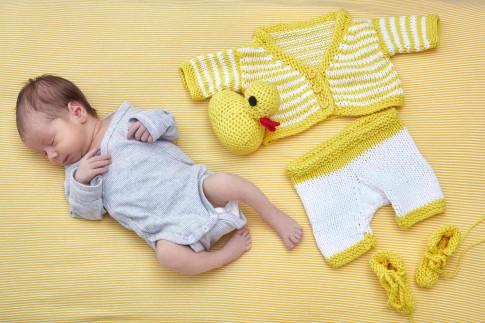 Das Baby liegt im hellgrauen Strampler auf einer gelben Decke. Neben ihm liegt selbstgestrickte Babykleidung. Ein weiß-gelbes Jäckchen, eine weiß - gelbe Hose, gelbe Schuhe und eine gelbe Ente mit rotem Schnabel.