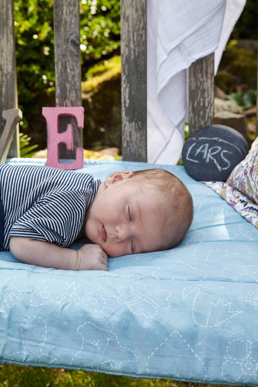 Das Baby liegt schlafend im Garten auf einer Holzbank. Unter ihm eine hellblaue Decke. Auf einem Stein ist der Name des Babies mit Kreide geschrieben. Ein weißes Tuch hängt über der Lehne der Holzbank.