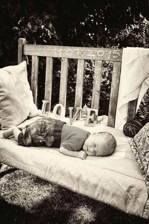 Foto in schwarz-weiß. Das Baby liegt schlafend im Garten auf einer Holzbank. Unter ihm eine Decke. Auf einem Stein ist der Name des Babies mit Kreide geschrieben. Ein helles Tuch hängt über der Lehne der Holzbank. Hinter dem Baby sind die Buchstaben LOVE. Auf der Bank steht mit Kreide das Geburtsdatum geschrieben. Zwei Kissen sind angelehnt.