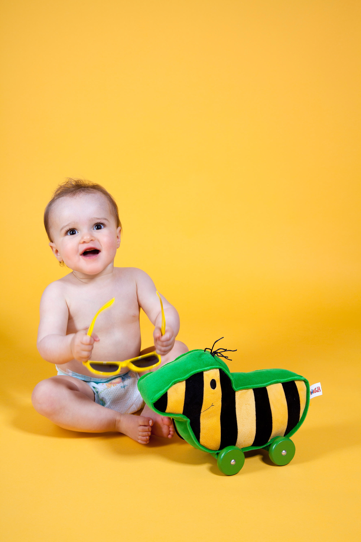 Das Baby sitzt mit einer Windel auf einem gelben Untergrund. Es hält eine gelbe Sonnenbrille in der Hand. Vor ihm steht eine schwarz-gelbe Ente mit grünen Rädern.