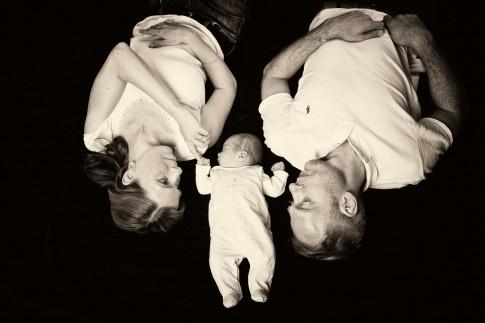 Familienfoto mit Vater, Mutter und Kind. Das Kind liegt zwischen den beiden. Das Baby hält den Finger der Mutter fest. Schwarz – weiß Foto.