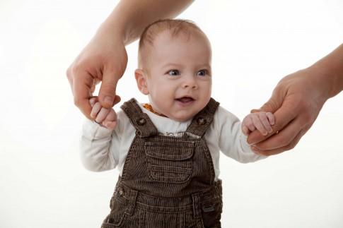 Das Kind hat eine braune Latzhose an und wird an den Händen gehalten.