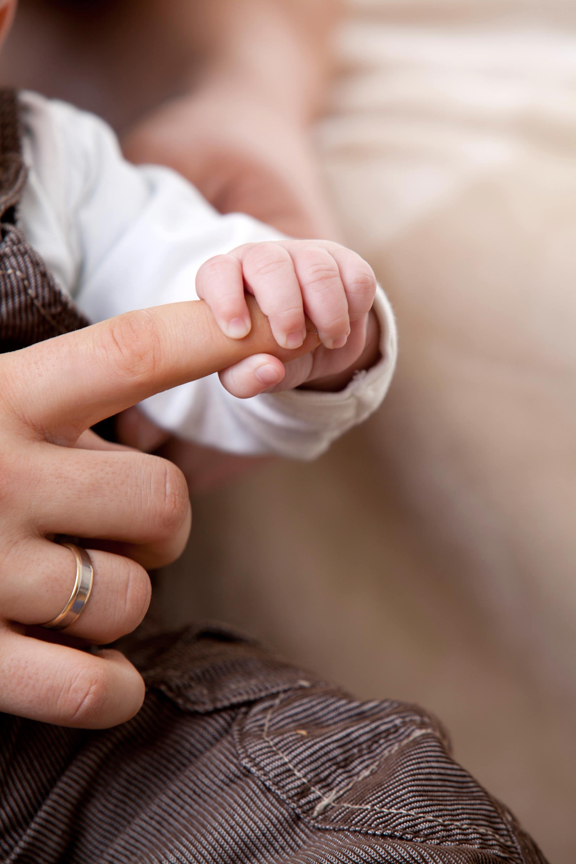 Detailaufnahmen einer Kinderhand, die einen Zeigefinger festhält.