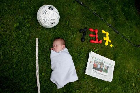 Inszenierung mit einem Baby. Es ist in ein Tuch gewickelt. Das Baby liegt auf dem Rasen und ist umgeben von einem Fussball, ein Maßband und eine Zeitung. Das Geburtsdatum ist in den Farben schwarz, rot, gold geschrieben.