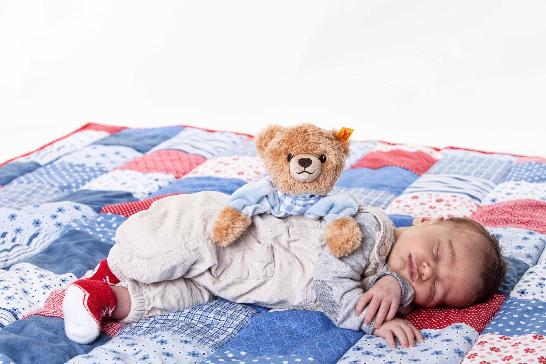 Das Baby liegt seitlich auf einer karierten Decke. Es trägt eine helle Latzhose und hat die Arme überkreuzt. Ein hellbrauner Kuschelbär mit blauem Pulli beugt sich über das schlafende Baby.