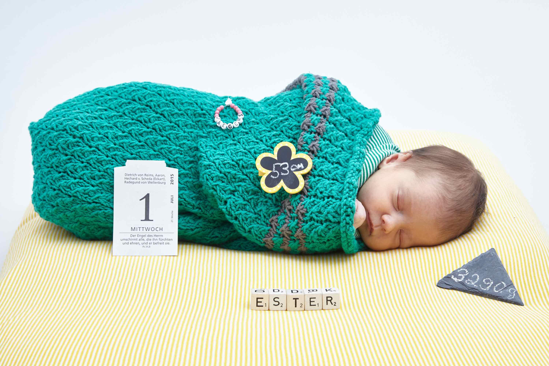 Inszenierung mit einem Baby. Es ist in eine grüne Decke gewickelt. Es liegt auf einem weiß -gelb - getreiftem Kissen. An der Decke ist ein Blumenanstecker mit der Zahl 53 cm angebracht. Das Baby ist umgeben von einem Kalenderblatt mit der Information 1 und Mittwoch. Vor ihm liegen 5 Würfel mit Buchstaben, mit den der Name des Kindes geschrieben wurde. Auf einer dreieckigen Steintafel wurde mit Kreide das Gewicht des Babies geschrieben. An der Decke ist ein kleines Armband befestigt.