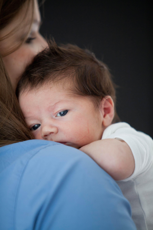 Das Kind guckt über die Schulter der Mutter. Sie hat ein blaues Hemd an.