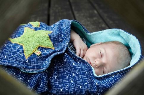 Das Baby schläft eingewickelt in einer blauen Decke mit grünem Stern.