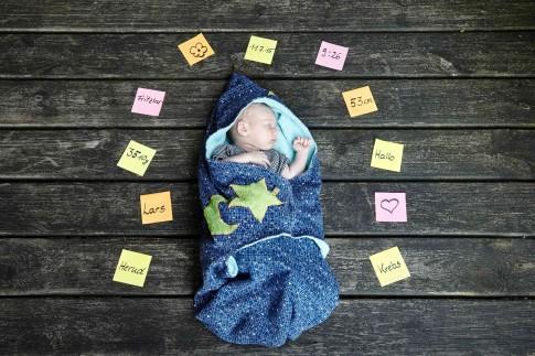 Das Baby schläft eingewickelt in einer blauen Decke mit grünem Mond und Stern. Es liegt auf Holzdielen und ist umgeben von farbigen Klebezetteln. Auf den Zetteln stehen Informationen über das Kind. Name, Gewicht, Geburtstort, Geburtsdatum, Uhrzeit, Größe und Sternzeichen. Die Zettel sind wie ein religiöser Heiligenschein angeordnet.