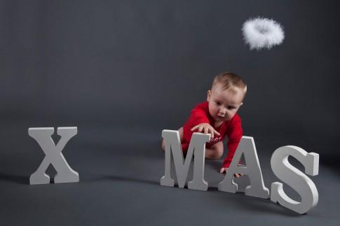 Das Kind hat einen roten Strampler an und greift nach einem Dekobuchstaben. Die Buchstaben XMAS sind weiss. Ein weißer Heiligenschein fliegt über dem Kopf des Kindes.
