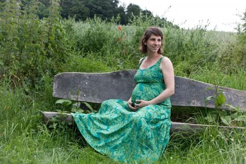 Babybauchshooting in der Natur. Die schwangere Frau sitzt im freien auf einer Holzbank. Um sie herum ist hohes Gras und im Hintergrund sind Bäume zu sehen. Die werdende Mutter hat ihre Hände stützend unter dem Babybauch liegen.