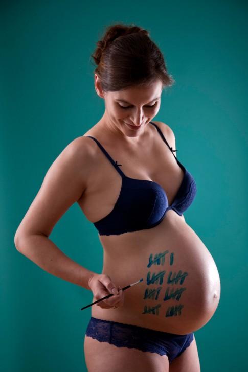 Die schwangere Frau hält einen Pinsel in der Hand. Der Babybauch ist mit Strichen versehen. Die Tage werden gezählt. Outfit der Frau in klassischer blauer Unterwäsche.