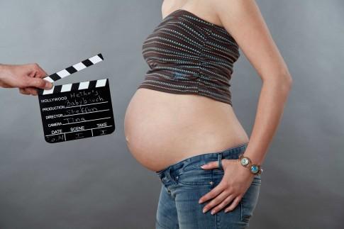 Babybauchshooting im Studio. Die werdende Mutter steht seitlich zur Kamera. Vor den Babybauch wird eine Filmklappe gehalten auf der die Namen der werdenden Eltern stehen und der der Fotografin.