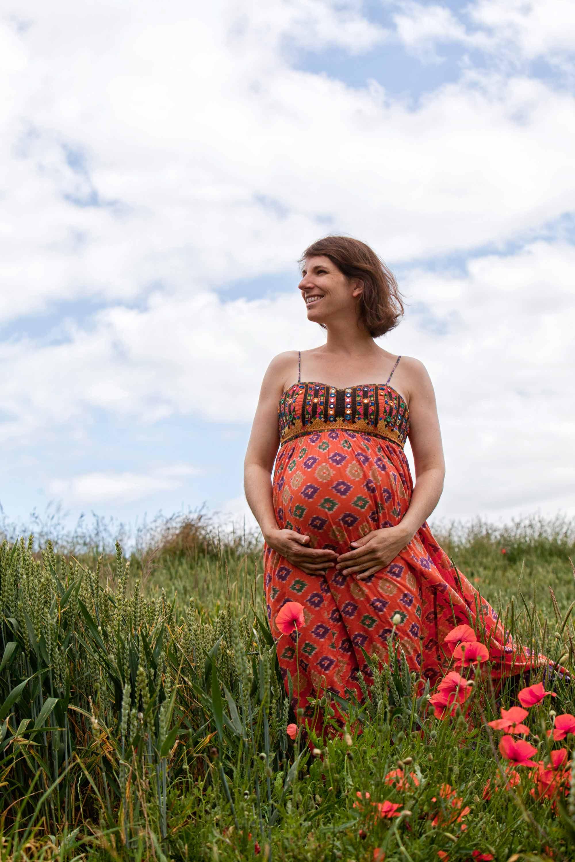 Schwangerschaftsshooting in einem Getreidefeld. Im Vordergrund sind Blumen zu sehen. Die Frau hält lächelnd ihre Hände unter den Babybauch. Sie trägt ein rotes Sommerkleid.
