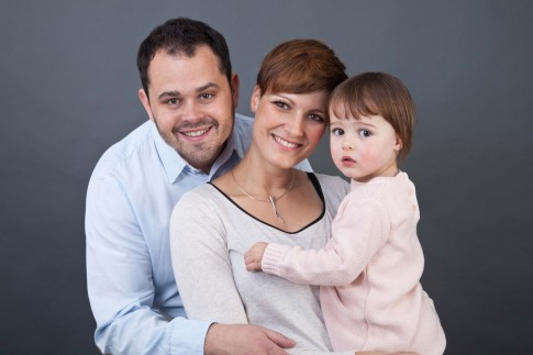 Vater, Mutter und Kind gucken in die Kamera. Die Mutter hält die Tochter auf dem Arm. Der Vater steht hinter seiner Frau und hält sie leicht umarmt.