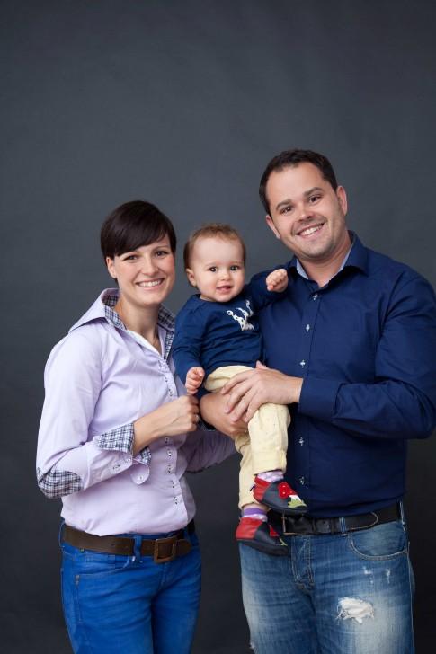 Dunkler Hintergrund im Fotostudio. Das Kind wird von den Eltern in der Mitte gehalten. Der Vater trägt das Kind. Alle gucken lächelnd in die Kamera.