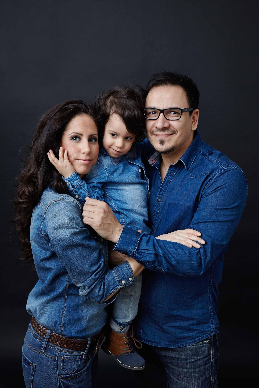 Einheitliches Outfit der Familie. Alle tragen Jeanshose und ein Jeans Oberteil. Der Vater und die Mutter stehen außen und tragen ihr Kind zwischen sich. Das Kind legt seine Hand um das Gesicht seiner Mutter.