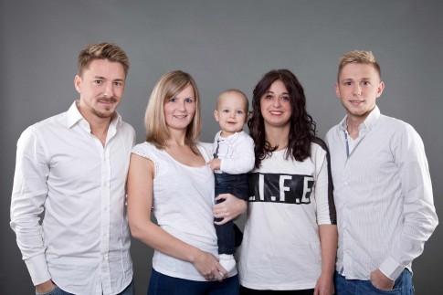 Familienshooting mit mehreren Familienmitgliedern. Außen stehen zwei Männer. Beide tragen ein weißes Hemd. Dazwischen stehen zwei Frauen, wovon die eine ein Kind in der Hand hält. Alle haben ein weißes Oberteil an.