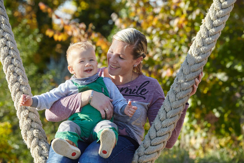 Familienshooting im Freien. Mutter und Kind sitzen auf einer Flechtschaukel. Die Mutter hält ihr Kind auf dem Schoss. Im Hintergrund sieht man Bäume.