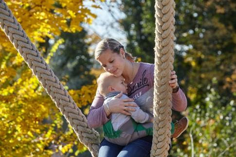 Familienshooting im Freien. Die Mutter hält ihr Kind schützend während des Schaukelns an sich gedrückt. Herbstliche Bäume sind im Hintergrund zu sehen.