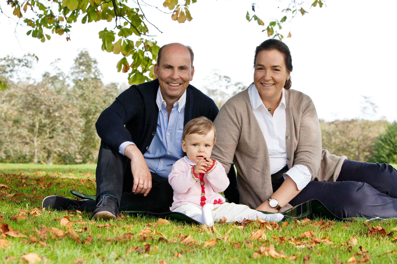 Die Familie sitzt auf einer Wiese. Die Eltern sitzen hinter dem Kind. Das Kind hält eine Kastanie in der Hand.