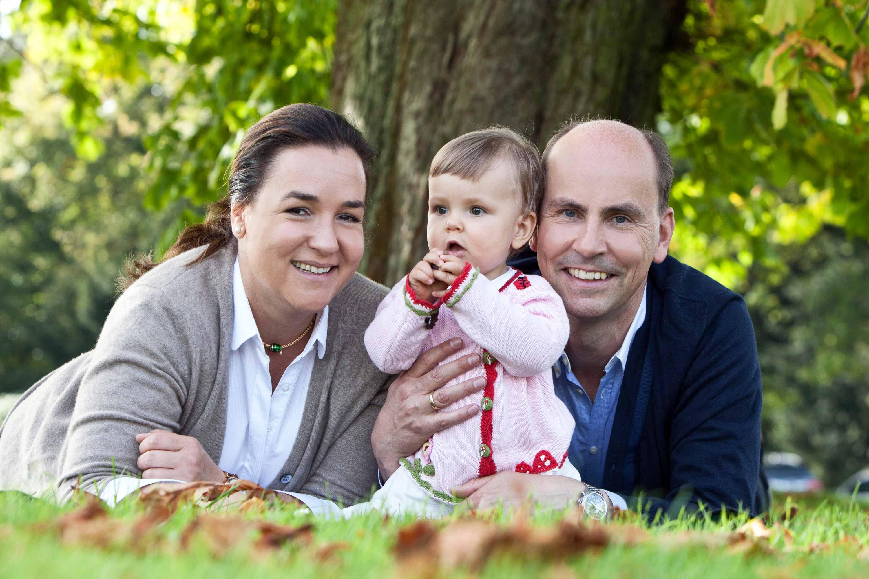 Die Eltern liegen auf dem Bauch auf einer Wiese. Ihr Kind sitzt vor ihnen. Ein Baum ist im Hintergrund zu sehen.
