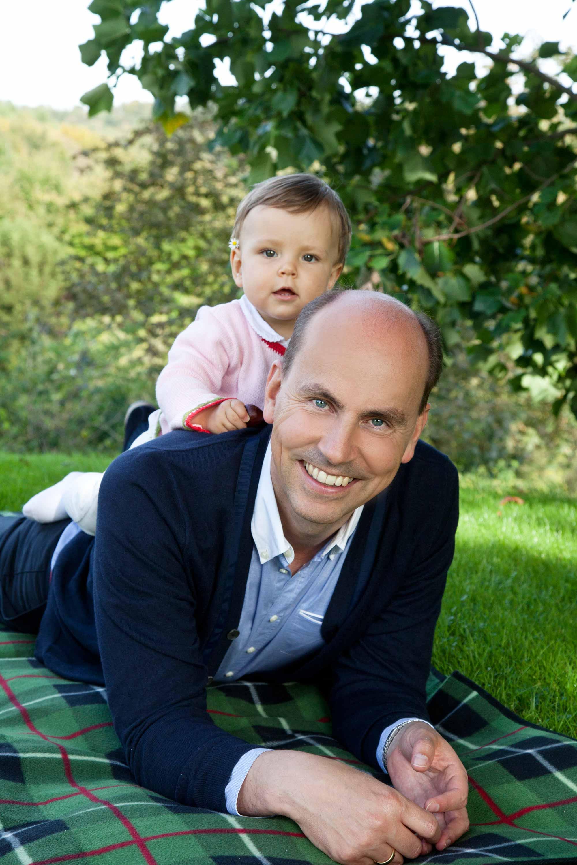 Der Vater liegt bei dem Familienshooting auf dem Bauch auf einer Decke. Sein Kind liegt auf seinem Rücken. Im Hintergrund ist die Wiese auf der das Shooting statt findet zu sehen und ein paar Bäume.