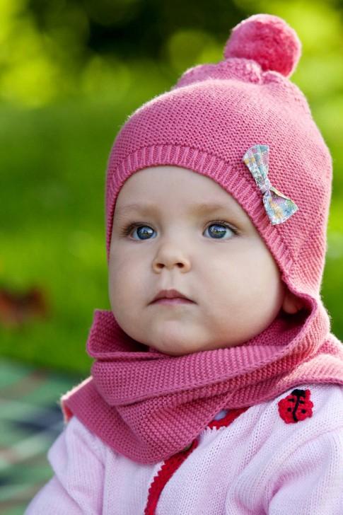 Ein Kinderportrait während des Familienshootings. Das Kleinkind trägt eine pinke Mütze und einen passenden Schal dazu. Im Hintergrund ist viel grün zu sehen, da dass Shooting im Freien statt findet.
