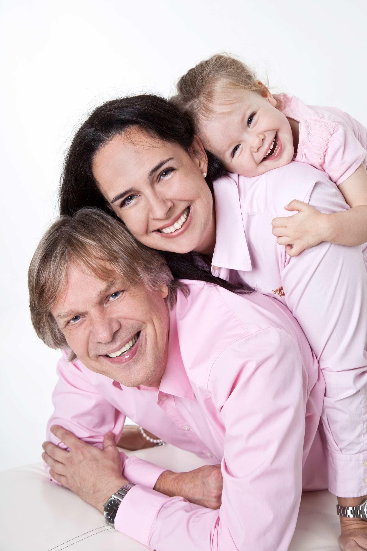 Familienshooting im Fotostudio. Übereinander gereiht liegen Vater, Mutter und Tochter auf einem weißen Untergrund. Die Familie trägt einheitlich rosa Oberteile. Alle gucken lächelnd in die Kamera.