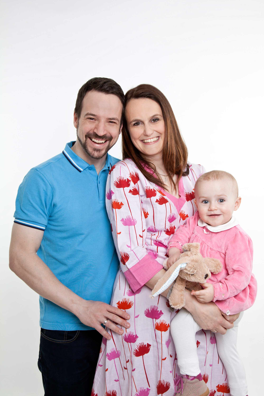 Familienshooting zu dritt. Vater und Mutter stehen beisammen und die Mutter hält die Tochter auf dem Arm. Die Tochter trägt einen Kuschelhasen in der Hand. Alle lächeln in die Kamera.