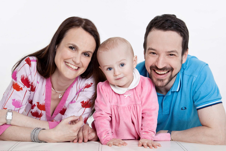 Mutter, Kind und Vater stützen sich auf einer Couch ab, vor der sie knien. Alle schauen in die Kamera. Der Hintergrund ist weiß.