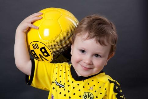 Einzelportrait eines Kindes. Der Hintergrund ist dunkel. Das Kind trägt ein BVB Trickot und hält lächelnd einen BVB Fußball auf seine Schulter.